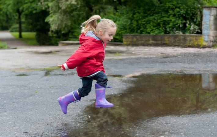 Happy child in rain boots and coat jumping into a puddle and engaging in unstructured play