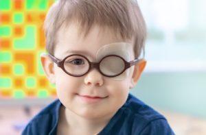 Young boy wearing an eye patch to treat amblyopia