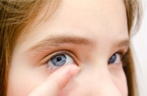 A close up of a little girl putting in a contact lens