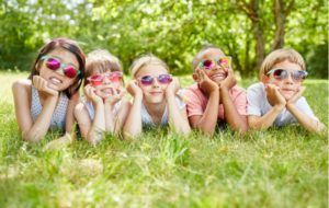 Six kids laying on the grass with sunglasses on to protect their eyes from the sun